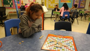 Mya concentrates on her word- she is playing Scrabble.
