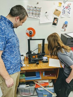 Teacher and student watch 3D printer in action