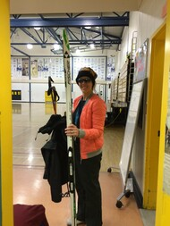 Teacher carrying ski equipment at gym