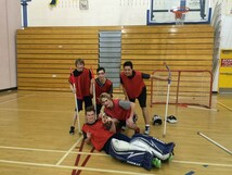 Students playing floor hockey at gym