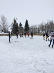Students playing hockey outside in winter