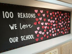 one hundred paper hearts with reasons students love school written on them