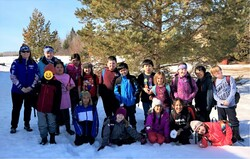 group of students posing in the snow in front of evergreen trees