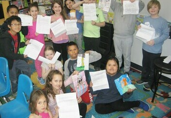 group of students proudly holding up pen pal letters