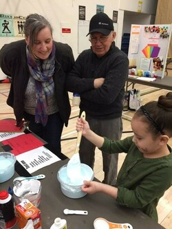 a young student demonstrates her science fair project to the judges