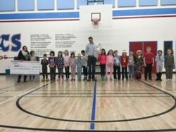 group of students posing with a donation check from a local business