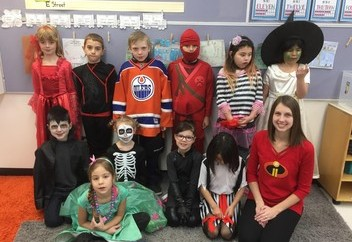 students and teacher in halloween costumes