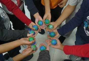 a circle of students hands with each one holding a clay model of the earth