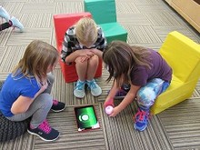 Three girls playing on an iPad at Learning Commons