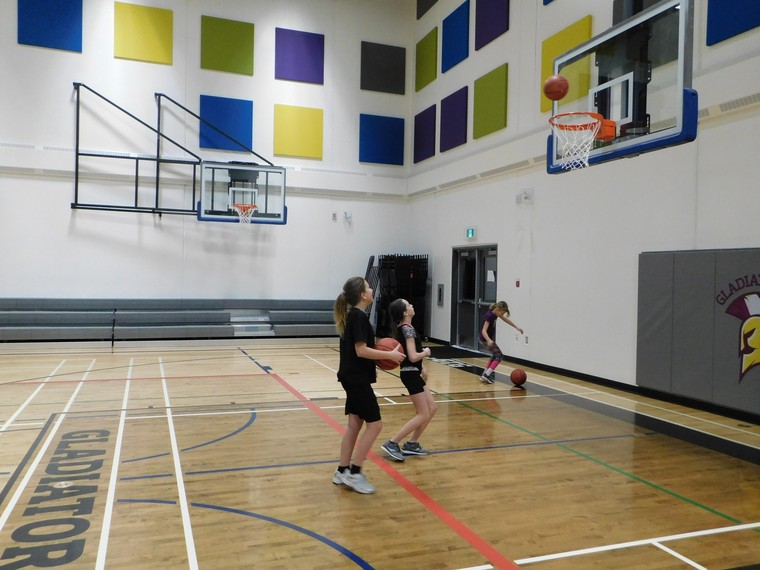 Girls practicing basketball shoots at gym